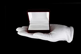 Plot: White gloved hand holding an open box
