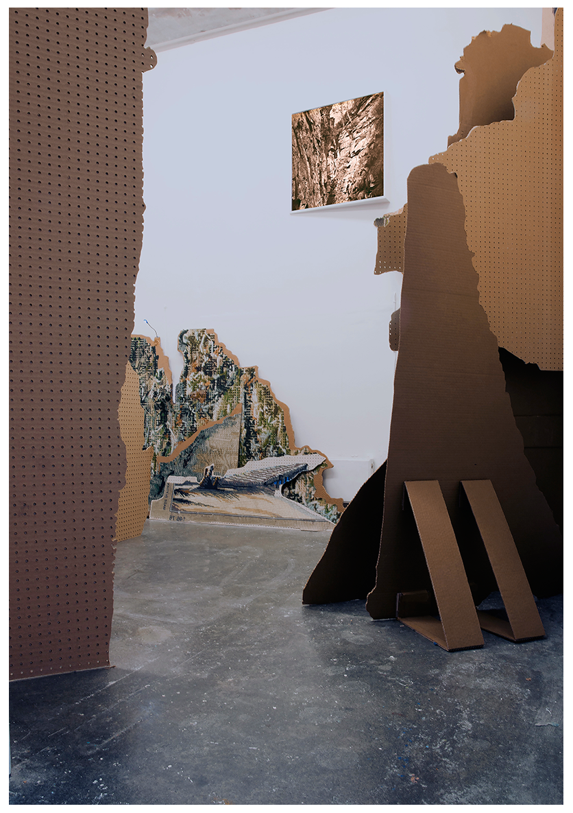 Monumental fragments of landscape stand in a room.