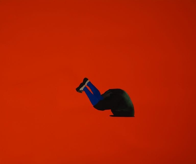 Slip: Against a fluorescent orange backdrop, a painted figure with blue hose and a dark green tunic falls headlong into a black hole