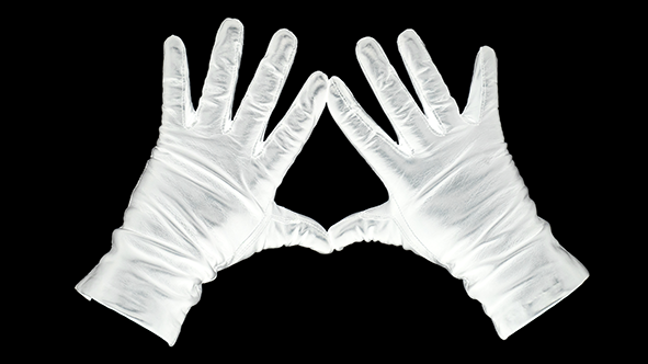 Gaga: Against a black background, white gloved hands splayed out with thumbs and forefingers touching to make a triangle
