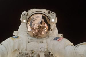 The Case of the Gold Ring: an astronaut with a gold visor looks at the camera against the blackness of space