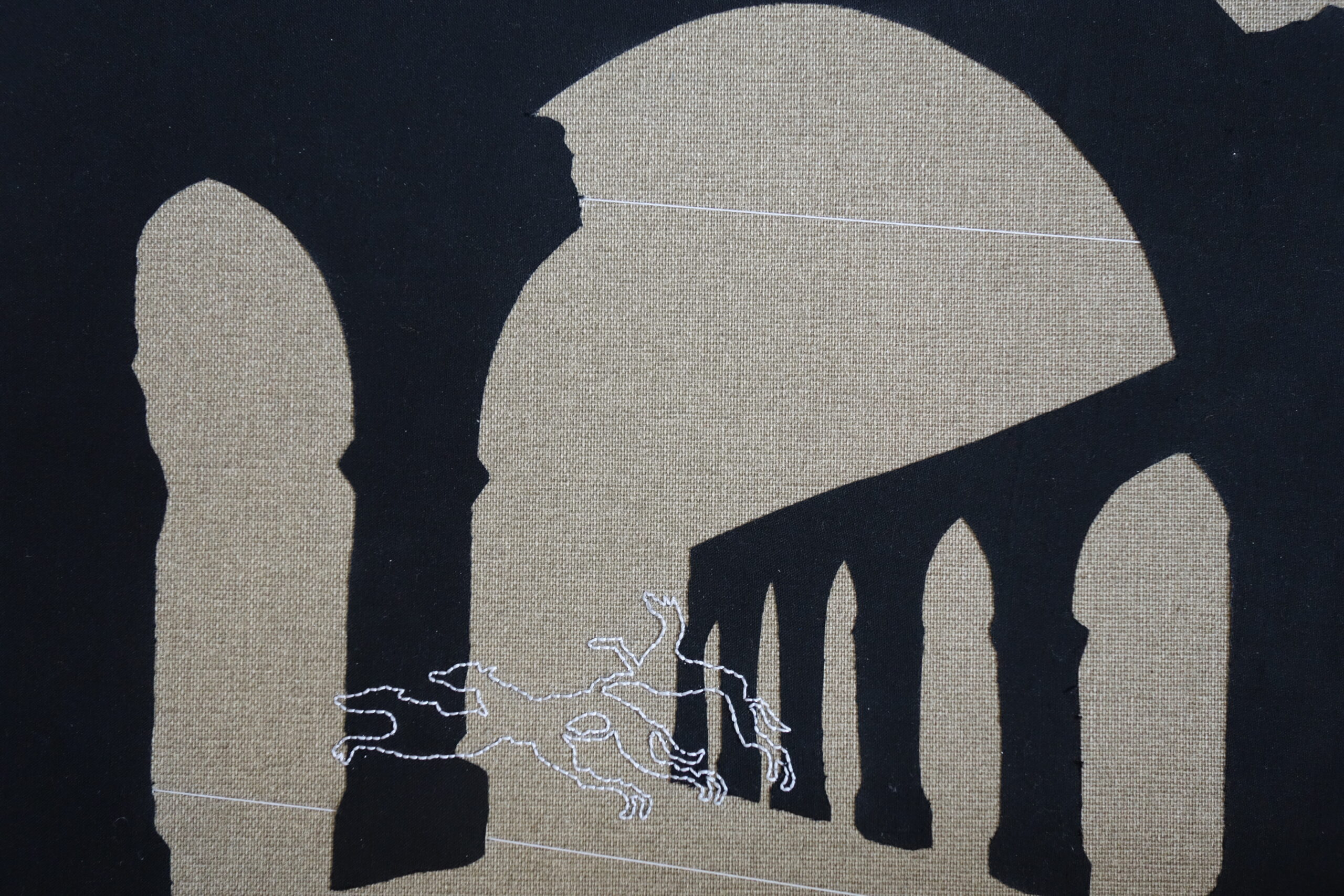 Black silhouettes of arches against a mid brown linen background, with greyhounds outlined in white embroidery