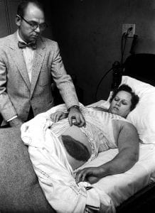 Stars Fell on Alabama: Black and white photograph of a woman lying in bed, a doctor at her side, holding the bedclothes back to show off a huge black bruise about 30cm long and 15cm wide.