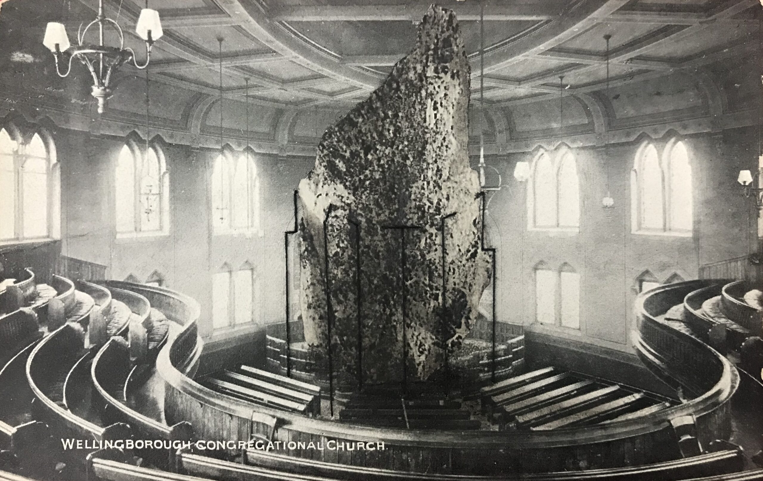 Black and white postcard of the inside of a large round building with shaped wooden seating surrounding a central dais. On the dais a huge rock reaches up to the ceiling, held in place with rods made of thread.