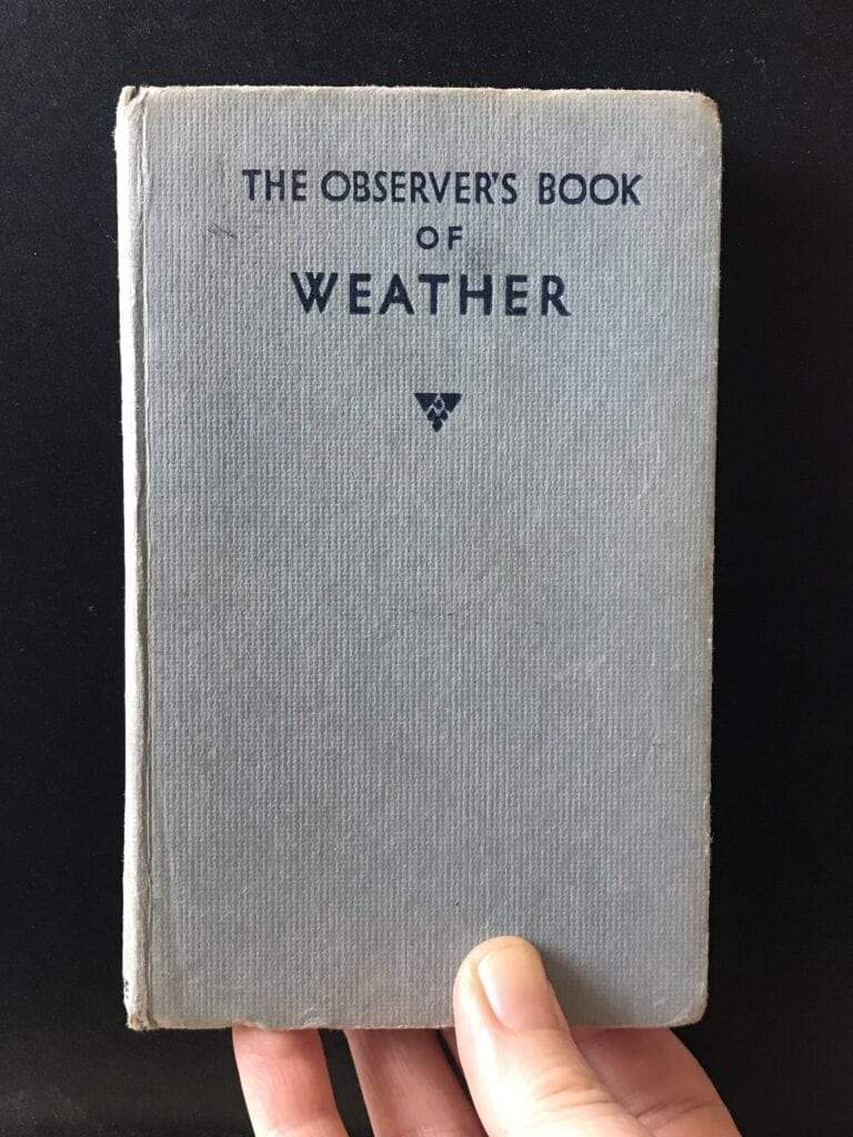 Through a glass, darkly: Hand holding The Observer Book of Weather