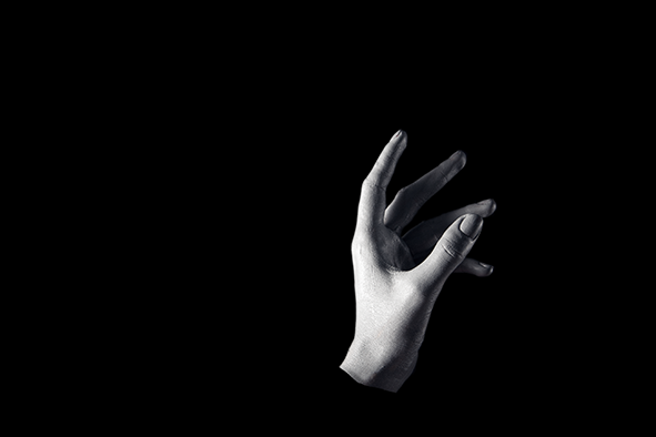 Sturgeon: A white painted left hand reaches up out of a black darkness as if from a lake at night