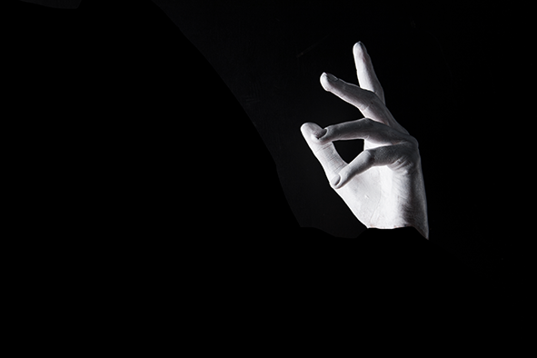 The kiss: a single left hand floats against a black background