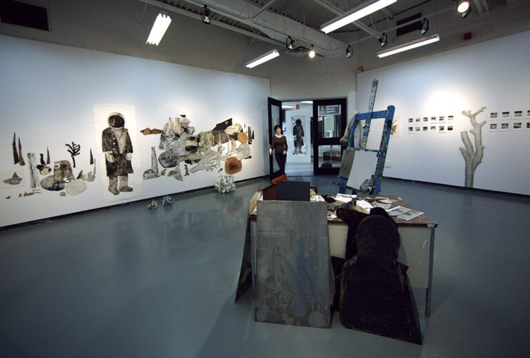 So pass away the old timers, one by one: view of a gallery with an installation in the middle of a room of an artist's desk