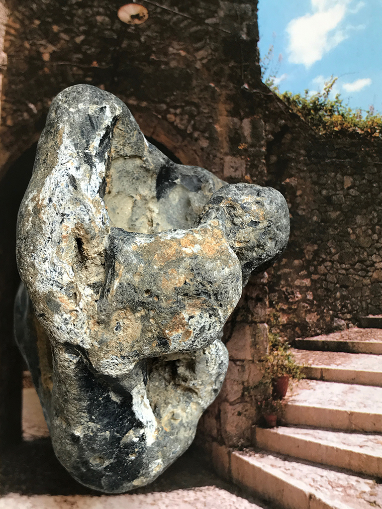 a meteorite poses next to an ancient stone archway and steps