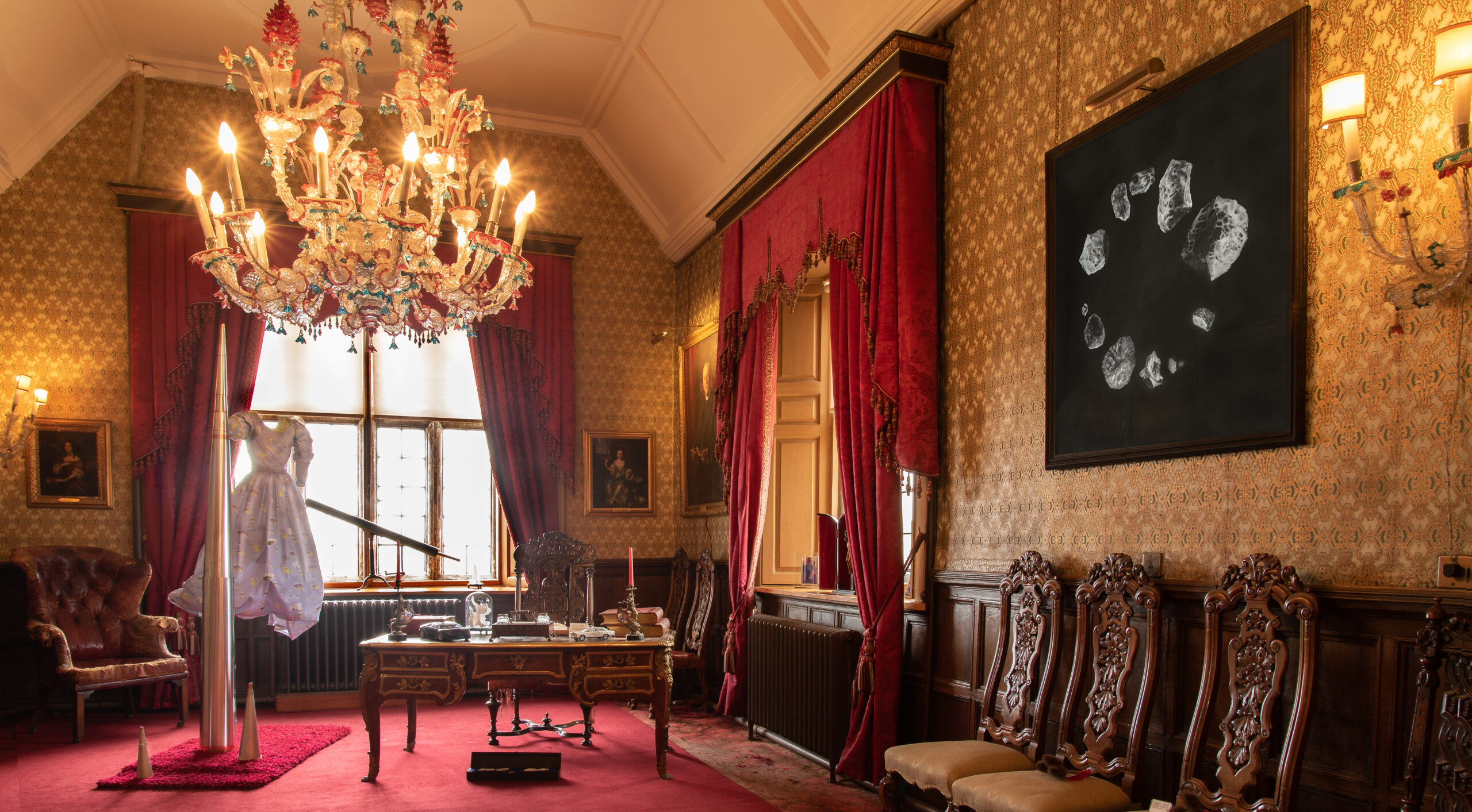 long, grand room inside a stately home, with a red carpet and gold and white wallpaper, fittings and ceiling mouldings. At the far end of the room a dress floats in the air next to a large metal cone; on the right hand wall a drawing on black paper can be seen